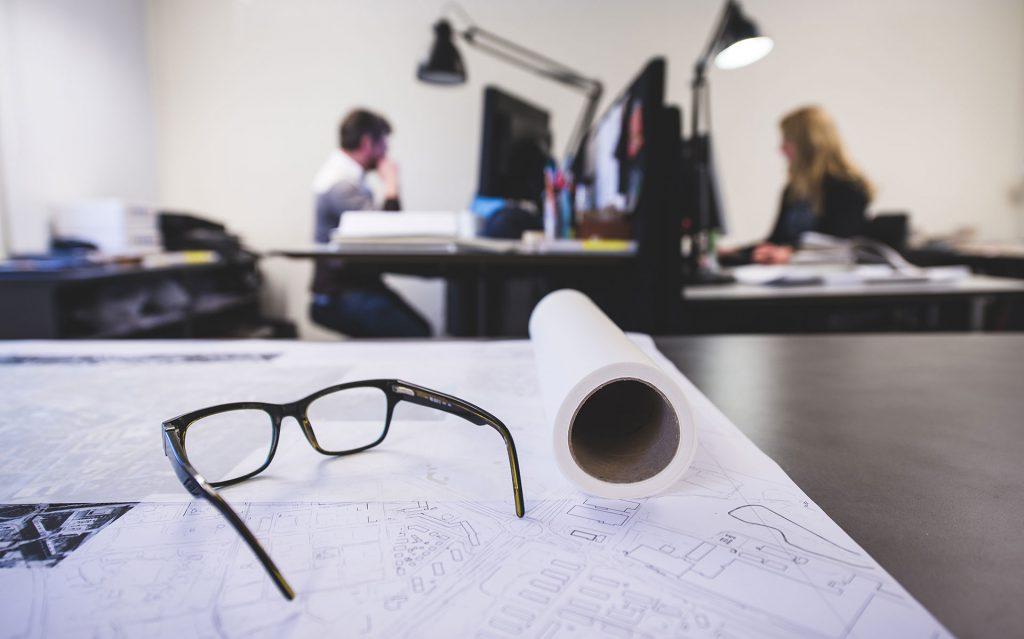 Glasögon i förgrunden och personer som jobbar i bakgrunden