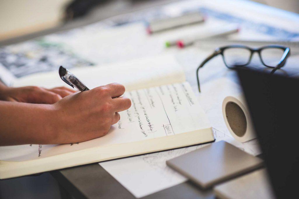 Person skriver i skissblock