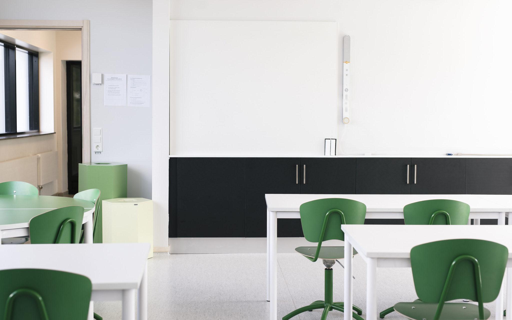 Vita bord och gröna stolar i klassrum
